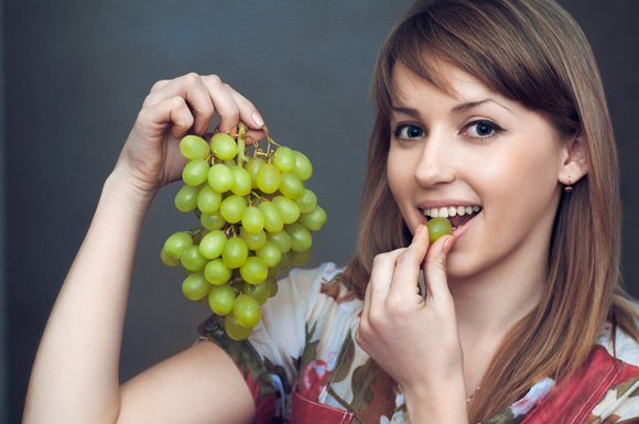 young-woman-eating-green-grapes