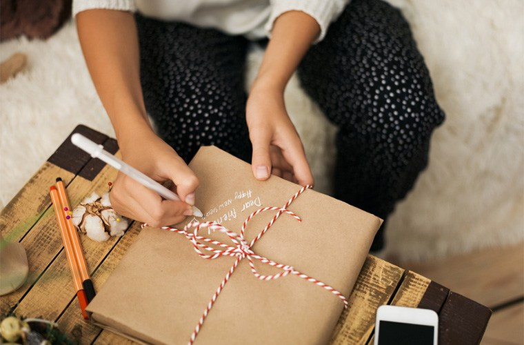Stocksy-Milles-Studio-Young-girl-wrapping-Christmas-Gifts-at-home